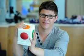 man with glasses holding a scoog, a white cube with coloured convex buttons on each face.