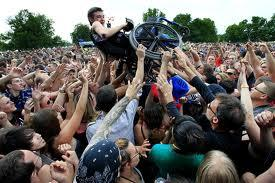 Person in wheelchair held up high within a crowd of people