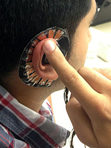 close up of man wearing an input device around his ear that he is pointing to with his index finger